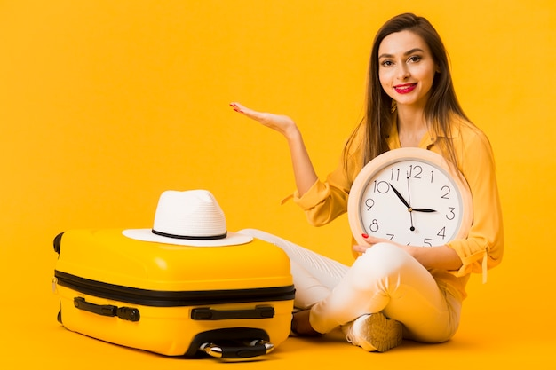 Woman posing with clock in hand next to luggage with hat on top