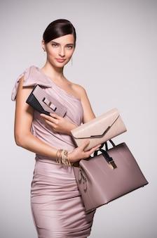 エレガントなドレスでクラッチとバッグでポーズをとる女性