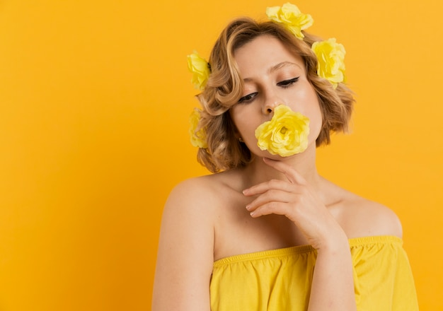 Woman posing with flower covering her mouth