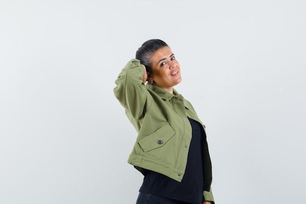 ジャケット、tシャツ、エレガントに見える頭の後ろに手でポーズをとる女性。