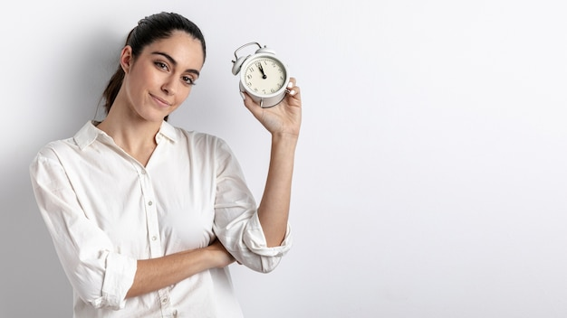 Woman posing with hand held clock and copy space