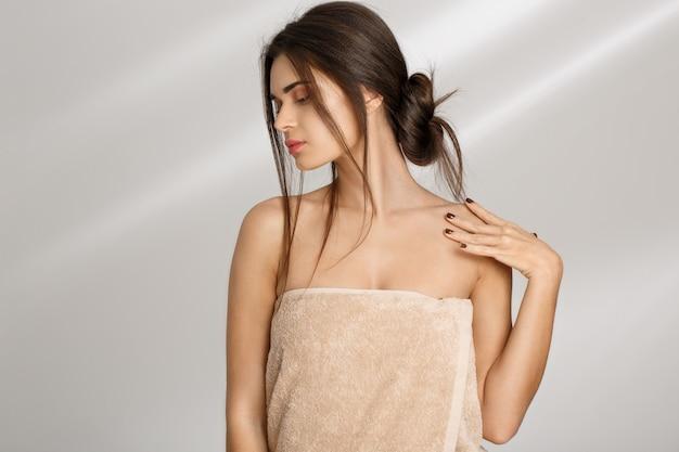 Женщина позирует с руки на плечо, глядя вниз. концепция релаксации.