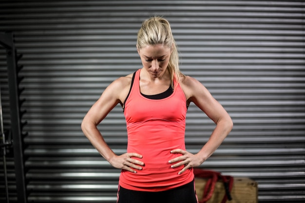 Woman posing with hands on hips at crossfit gym