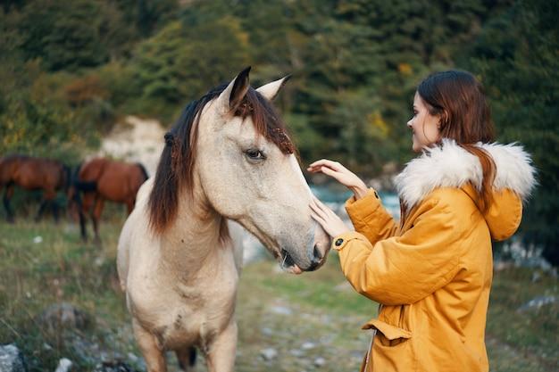 屋外で馬とポーズをとる女性