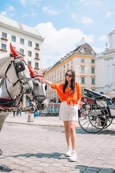 Женщина позирует с лошадьми в городе