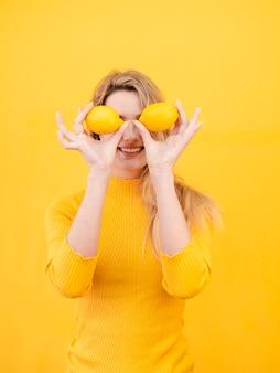 Donna che posa con i limoni