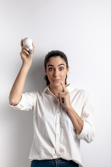 Woman posing with light bulb and copy space