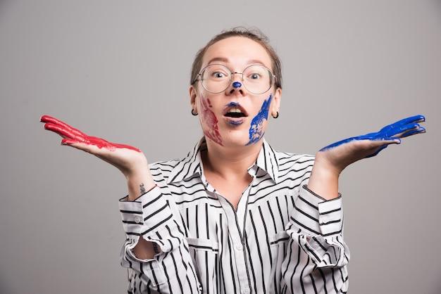 Женщина позирует с красками на лице на сером фоне. фото высокого качества