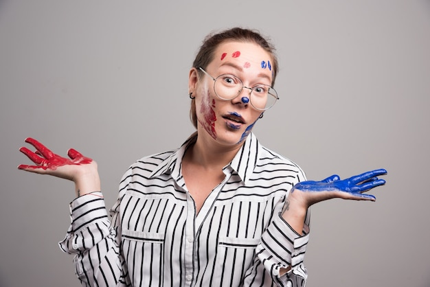 회색 바탕에 그녀의 얼굴에 페인트와 함께 포즈를 취하는 여자. 고품질 사진