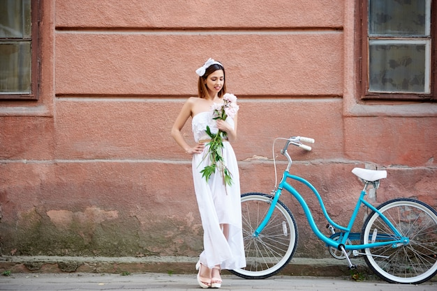 Woman posing with peonies and blue vintage bike with red historical building wall on background during summer day