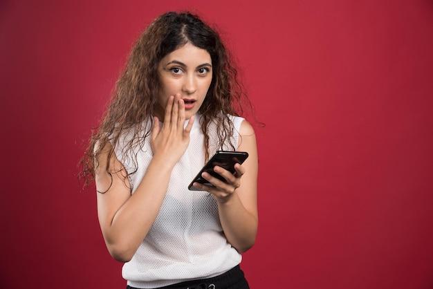 赤い携帯電話でポーズをとる女性