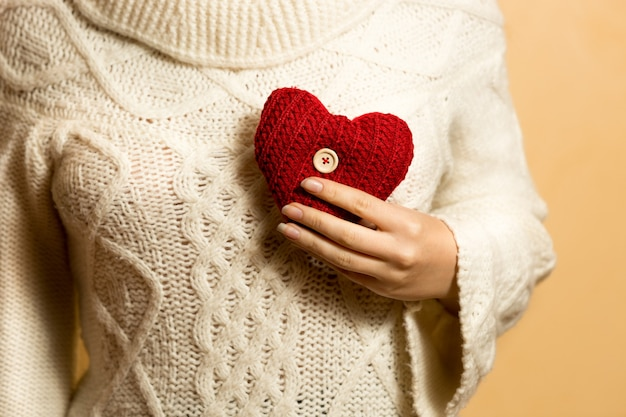 Женщина позирует с красным вязанным сердцем на груди
