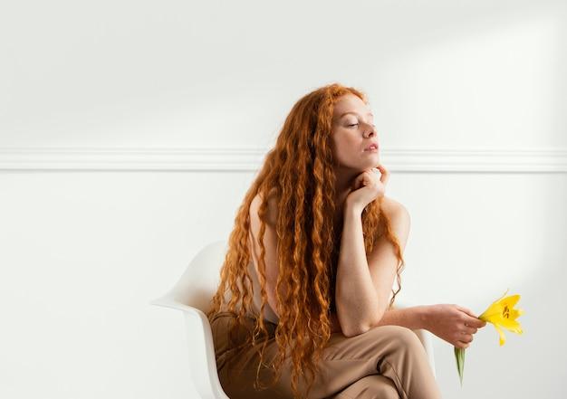 안락의 자에 봄 꽃과 함께 포즈를 취하는 여자