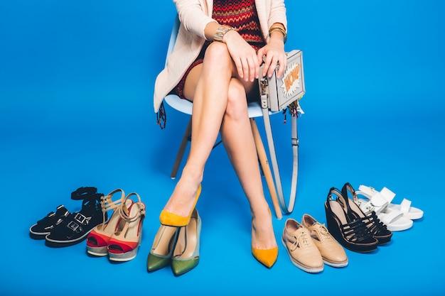 Женщина позирует в стильной обуви летней моды и сумке, длинные ноги, покупки
