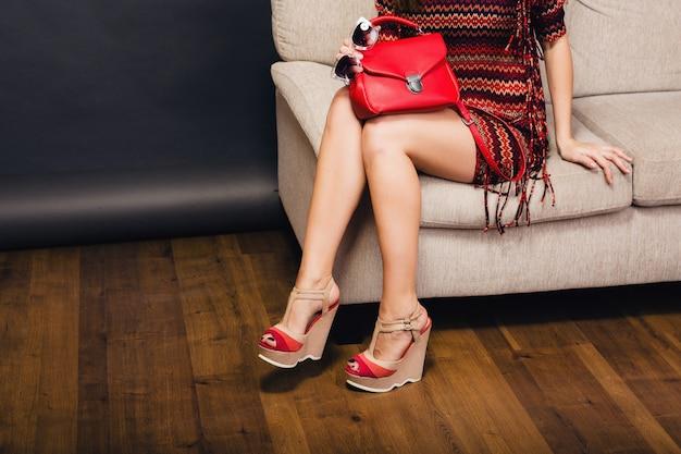 女性がスタイリッシュな靴夏のファッションとバッグでポーズ