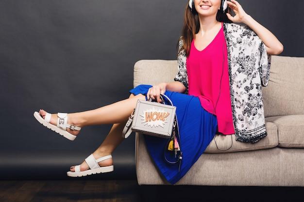 Donna che posa con la borsa e la moda estiva di calzature alla moda