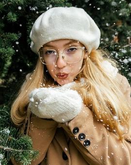 冬の公園で植物と吹雪でポーズをとる女性