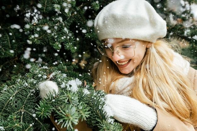冬の公園で植物と雪でポーズをとる女性