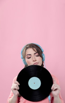 Woman posing with vinyl record while wearing headphones and copy space