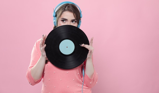 Woman posing with vinyl record while wearing headphones