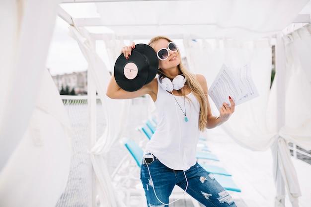 ビニールのレコードでポーズをとっている女性