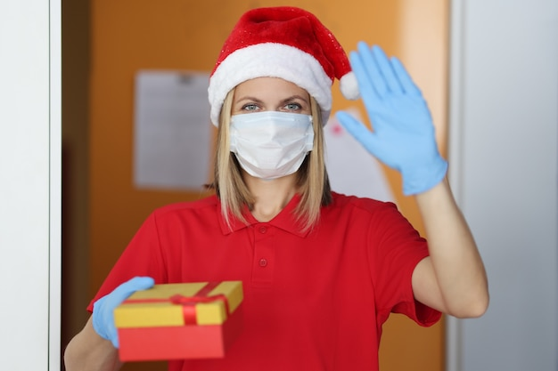 Woman postman in santa claus hat in medical mask and rubber gloves holds gift in her hand and waves hello