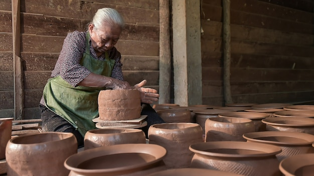 A woman potter in a plaid shirt and green apron beautifully sculpts a deep bowl