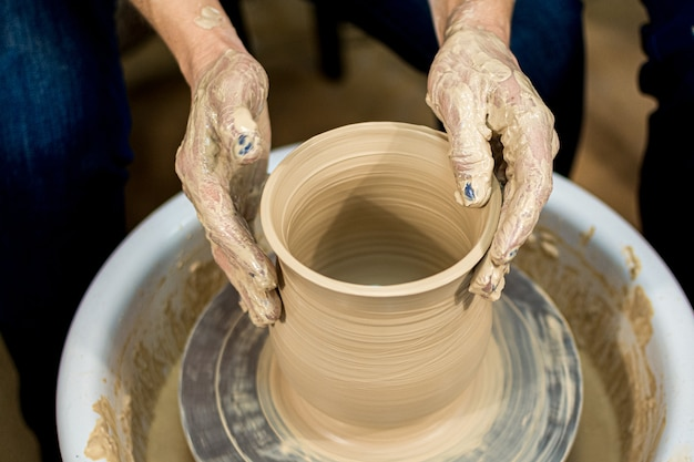 The woman potter's hands formed by a clay pot on a potter's wheel. the potter works in a workshop.