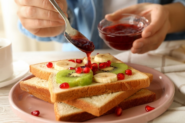 Woman pour jam on tasty toast with fruits