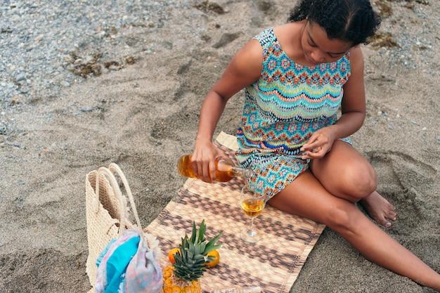 ビーチでグラスワインを注ぐ女性