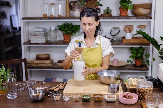 Женщина наливает миндальное молоко в стеклянную бутылку