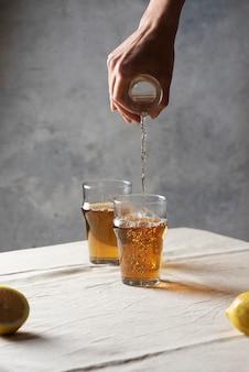ミニマリズムスタイルで、グラスに黒の熱いお茶を注ぐ女性