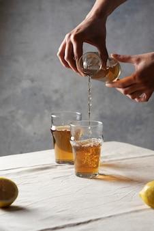 Женщина наливает черный горячий чай в стакан, изображение выборочного фокуса в стиле минимализма