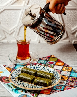Woman pouring black tea from french press served with turkish dessert