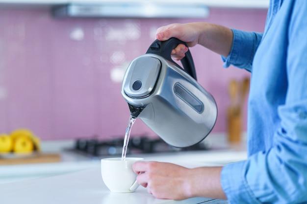 自宅の台所で熱いお茶を醸造するための電気ポットからカップに沸騰したお湯を注ぐ女性
