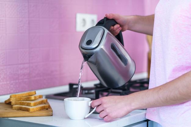 自宅のキッチンで熱いお茶を醸造するためのカップに電気ポットから沸騰したお湯を注ぐ女性