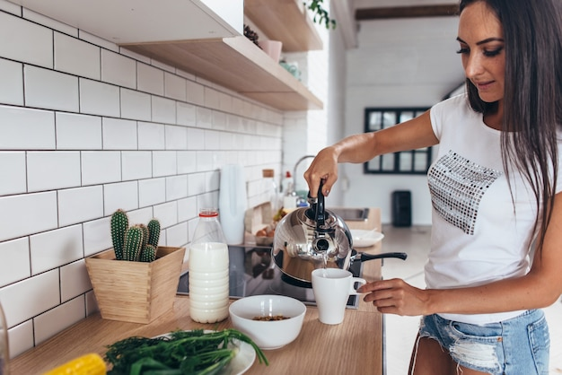 주전자에서 컵에 끓는 물을 붓는 여자.