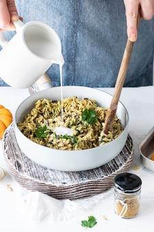 Donna versando il latte di cocco su riso al curry e coriandolo