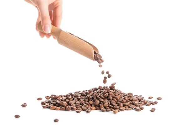 Женщина, разливая кофейные зерна на белом