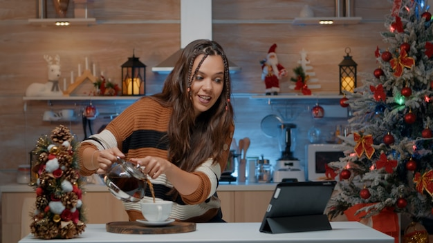 Woman pouring coffee while chatting on video call
