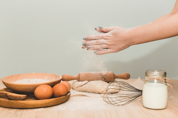 Woman pouring dough with flour
