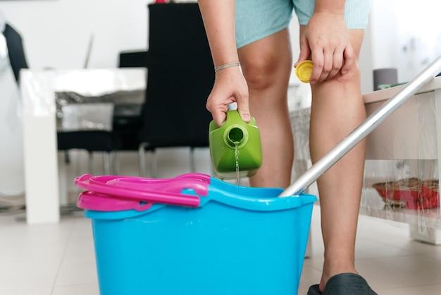 Женщина наливает средство для уборки пола в ведро со шваброй