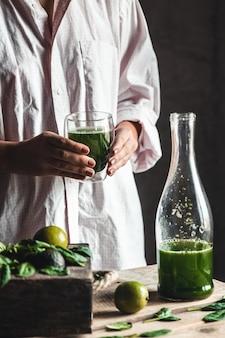 素朴な木製のテーブルの上に食材を入れたガラスの瓶に新鮮なブレンドの緑と白のスムージーを注ぐ女性。健康的な食事とライフスタイルのコンセプト。デトックスダイエット。レシピのアイデア。