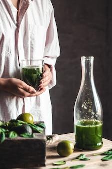 素朴な木製のテーブルの上に材料と一緒にガラスの瓶に新鮮なブレンドの緑と白のスムージーを注ぐ女性。健康的な食事とライフスタイルのコンセプト。デトックスダイエット。レシピのアイデア。
