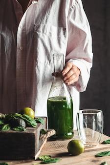 素朴な木製のテーブルの上に周りの食材とガラスの瓶に新鮮なブレンドの緑と白のスムージーを注ぐ女性