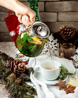 Woman pouring ginger tea with mint leave lemon and honey into cup