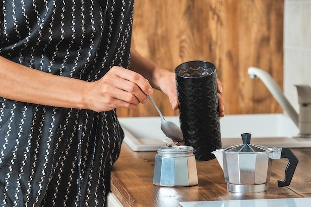 Женщина наливает молотый кофе в кофеварку