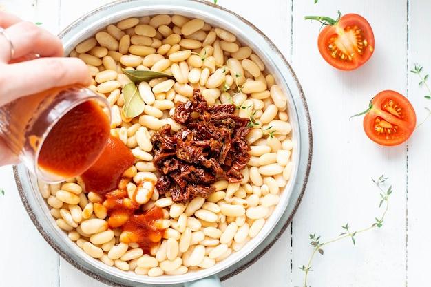 豆の入った鍋に自家製トマトソースを注ぐ女性