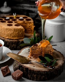 Woman pouring honey over honey cake with chocolate cream