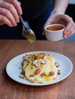 木製のテーブルの上のナッツとおいしいパンケーキに蜂蜜を注ぐ女性。素朴なスタイルの静物。おいしい自家製の朝食。